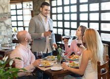 Young people enjoying food at tavern Royalty Free Stock Image