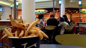 Young people enjoying meal at food court with front motion blur fries. Young people enjoying meal modern mall food court cafeteria with front motion blur fries stock video footage