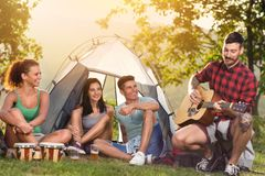 Young people enjoying in  music on camping trip. Sitting next tent and singing with guitar stock image