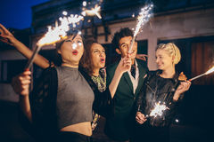 Young people enjoying new years eve with fireworks. Group of friends enjoying out with sparklers on city street. Young people enjoying new years eve with Stock Image