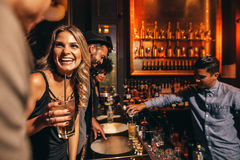 Young people enjoying a night at club. Beautiful young women with her friends at bar. Young people enjoying a night at club Royalty Free Stock Photos
