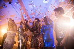Young People Enjoying Raving Party. Group  of beautiful young women wearing glittering dresses dancing under golden confetti shower enjoying  party in nightclub Stock Photo