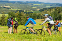People hiking, riding bicycles on springtime weekend Stock Images