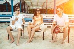 Young people enjoying summer vacation sunbathing drinking at beach bar Royalty Free Stock Image