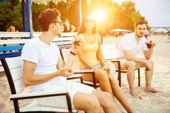 Young people enjoying summer vacation sunbathing drinking at beach bar Royalty Free Stock Photo