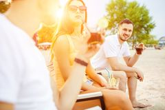Young people enjoying summer vacation sunbathing drinking at beach bar. Lifestyle Young people enjoying summer vacation sunbathing drinking at beach bar. Two royalty free stock photography