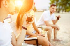 Young people enjoying summer vacation sunbathing drinking at beach bar Stock Image