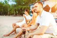 Young people enjoying summer vacation sunbathing drinking at beach bar Stock Photo
