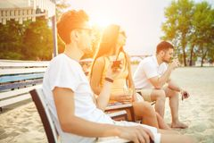 Young people enjoying summer vacation sunbathing drinking at beach bar Royalty Free Stock Photography