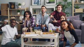 Young people enjoying video games laughing having fun at home together