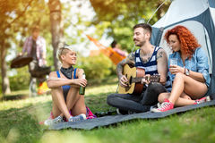 Young people enjoys on excursion with beer and guitar. At camp in forest stock photography