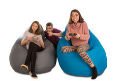 Young people are enthusiastic about playing video games while si. Tting on blue and grey beanbag chairs for living room or other room isolated on white Stock Photos