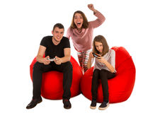 Young people are enthusiastic about playing video games while si. Tting on red beanbag chairs  on white background Royalty Free Stock Images