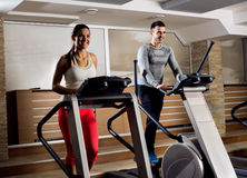 Young people on exercise machine in gym doing cardio Stock Image