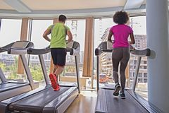 People exercisinng a cardio on treadmill in gym Stock Image