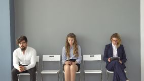 Young people expect interviews sitting on chairs in an office building. the interview for the job. recruits are bored. And enjoy the gadgets Stock Photography
