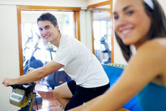 Young people with fitness bicycle in the gym. Royalty Free Stock Images