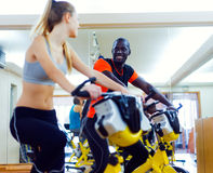 Young people with fitness bicycle in the gym. Stock Image