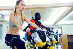 Young people with fitness bicycle in the gym. Royalty Free Stock Image