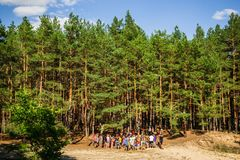 Young People in Forest wide horizontal. Kyiliv, Kyiv region, Ukraine - 08 09 2017: A group of young people teenagers in a pine forest play rest are competing Royalty Free Stock Image