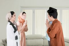 Young people forgiving each other at home. Young people forgiving each other by giving greet hands during Eid Mubarak celebration at home stock image