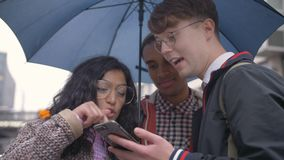 Young people are friends of different nationalities came under rain in Berlin and studying the transport scheme and. Young people friends of different stock video