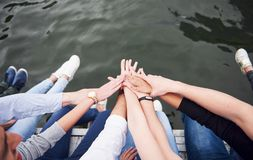 Young people friends sitting on the river bridge, lifestyle, feet over blue water.  Stock Images