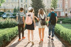 Young people friends walking in the city, a group of teenagers talking smiling having fun in the city, view from the back. royalty free stock photography