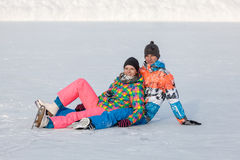 Young people, friends, winter ice-skating on the frozen lake Stock Photography