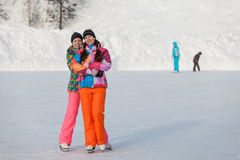 Young people, friends, winter ice-skating on the frozen lake Stock Images