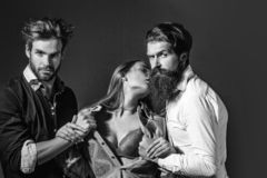 Young people or friends. Of two bearded handsome men hipsters with beards and pretty cute girl or sexi beautiful women in red bra on grey wall stock photos