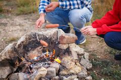 Young people fry appetizing sausages on fire. Outdoors. stock photo