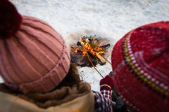 Young people fry marshmallow in the winter in the forest. Close up Royalty Free Stock Image