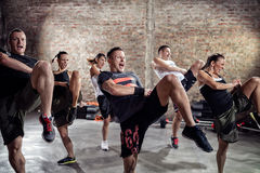 Young people full of energy doing exercise stock photography