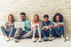 Young people with gadgets. Beautiful young people of different nationalities are using gadgets and smiling, sitting against white brick wall Stock Images