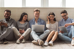 Young people with gadgets. Group of beautiful young people in casual clothes using gadgets and smiling while sitting together on the floor Royalty Free Stock Photos