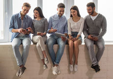 Young people with gadgets. Group of beautiful young people in casual clothes are using gadgets, talking and smiling while sitting together on the window sill Stock Photography