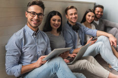 Young people with gadgets. Group of beautiful students in casual clothes using gadgets and smiling while sitting together on the floor Stock Photo