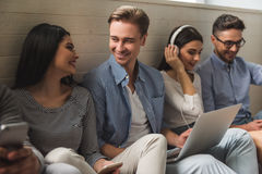 Young people with gadgets. Group of beautiful students in casual clothes using gadgets, talking and smiling while sitting together on the floor Royalty Free Stock Image