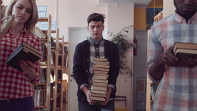 Young people gathering pile of books stock video footage