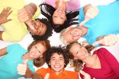 Young people gesturing thumb up sign. Young people lying down,gesturing thumb up sign Royalty Free Stock Images