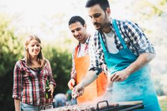 Young people grilling outdoors and smiling happy royalty free stock photos
