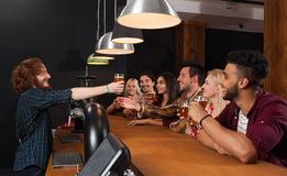 Young People Group In Bar, Barman Give Beer, Friends Sitting At Wooden Counter Pub,  Communication. Young People Group In Bar, Barman Give Beer, Friends Sitting Stock Photo