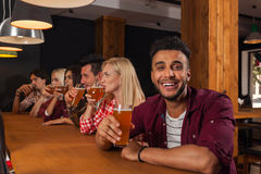 Young People Group In Bar, Drink Beer, Hispanic Man Hold Glass Toasting, Friends Sitting At Wooden Counter Pub. Communication Party Celebration Stock Image