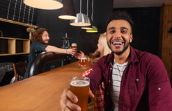 Young People Group In Bar, Hispanic Man Hold Glass Toasting Happy Smiling, Friends Sitting At Wooden Counter Pub. Communication Party Celebration Royalty Free Stock Images