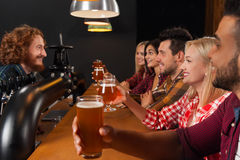 Young People Group In Bar, Hold Beer Glasses, Friends Sitting At Wooden Counter Pub,  Toast. Young People Group In Bar, Hold Beer Glasses, Friends Sitting At Stock Images