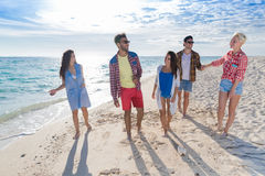 Young People Group On Beach Summer Vacation, Happy Smiling Friends Walking Seaside. Sea Ocean Holiday Travel stock photography