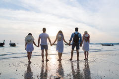 Young People Group On Beach At Sunset Summer Vacation, Friends Walking Seaside Back Rear View. Sea Ocean Holiday Travel royalty free stock images