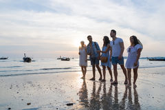 Young People Group On Beach At Sunset Summer Vacation, Friends Walking Seaside. Sea Ocean Holiday Travel stock image