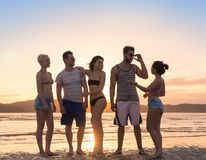 Young People Group On Beach At Sunset Summer Vacation, Happy Smiling Friends Walking Seaside. Sea Ocean Holiday Travel Royalty Free Stock Photos